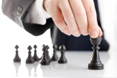 12066752-business-man-moving-chess-figure-with-team-behind--strategy-or-leadership-concept